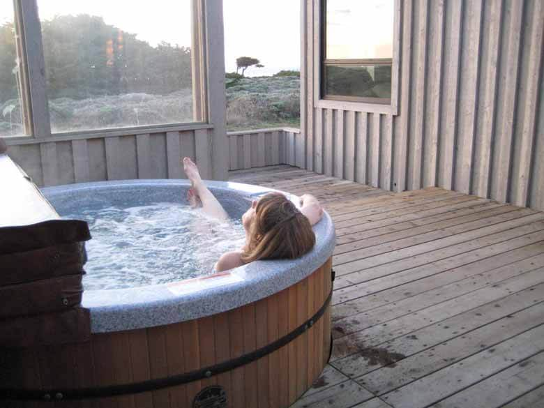 Glass enclosed deck with hot tub and a woman in it.