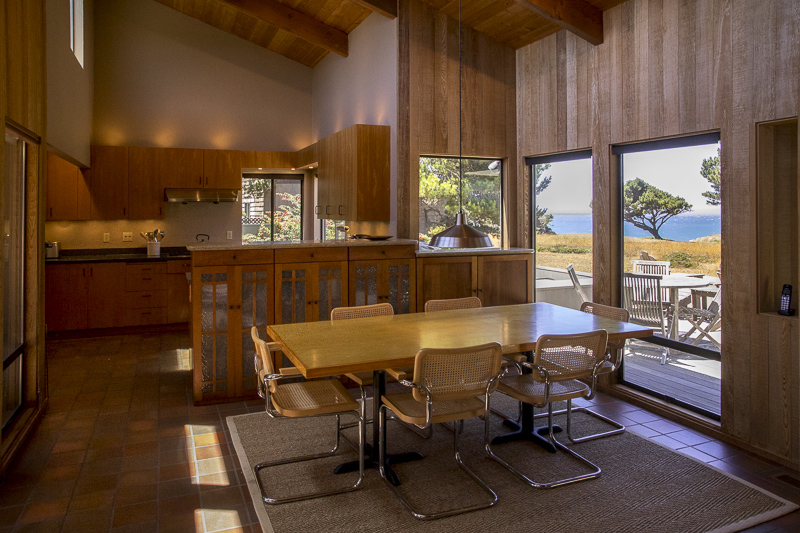 Dining room table with six chairs with kitchen beyond.  View outside to deck and on to ocean.
