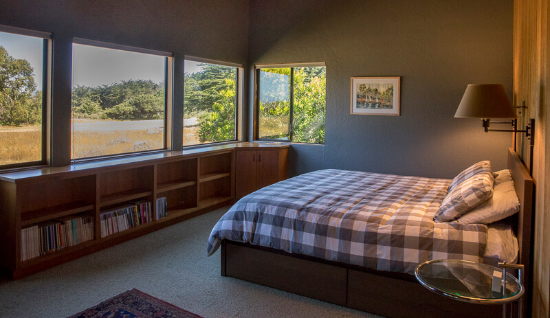 Bedroom with bed and bookshelves.  A view of the golf course fairway.