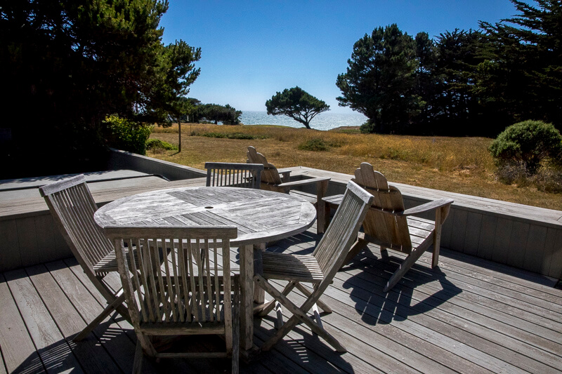 Deck with table, six chairs and a view of the ocean.