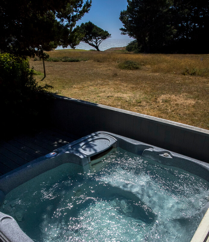 Hot tub with view across golf course fairway to ocean.
