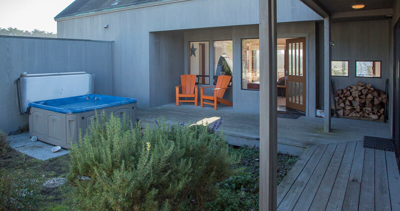 Garden, hot tub, two chairs and back deck of home with door open to living room.