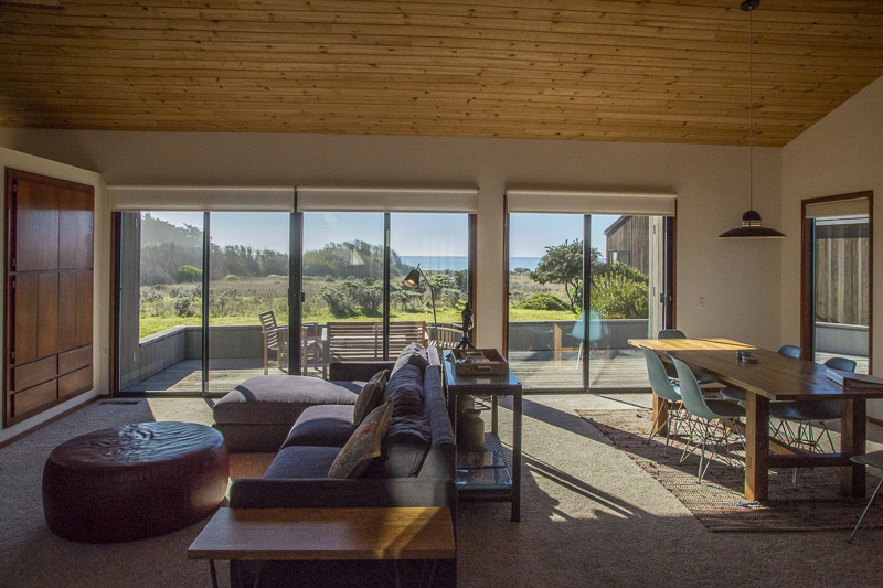 Living room and dining room with view across meadow to ocean.
