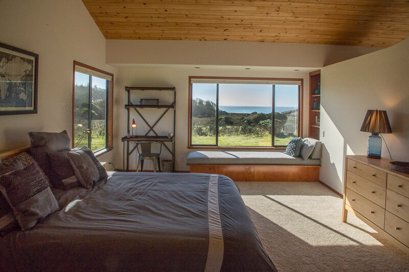 Bedroom - bed, chest of drawers, lamp, window seat and view across meadow to ocean.