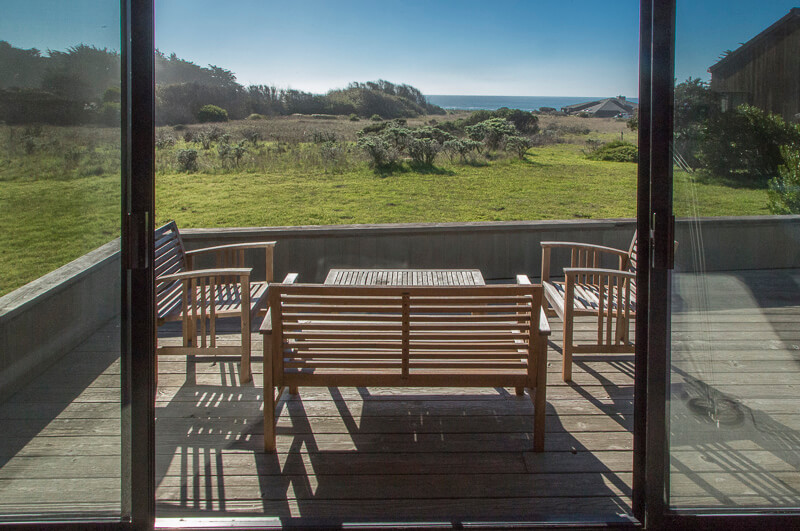 Deck with bench, two chairs, table and view across meadow to ocean.