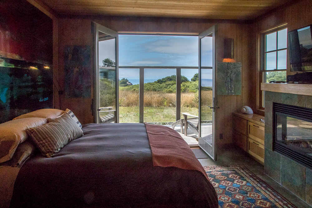 Bedroom with view across meadow to ocean through open doors.