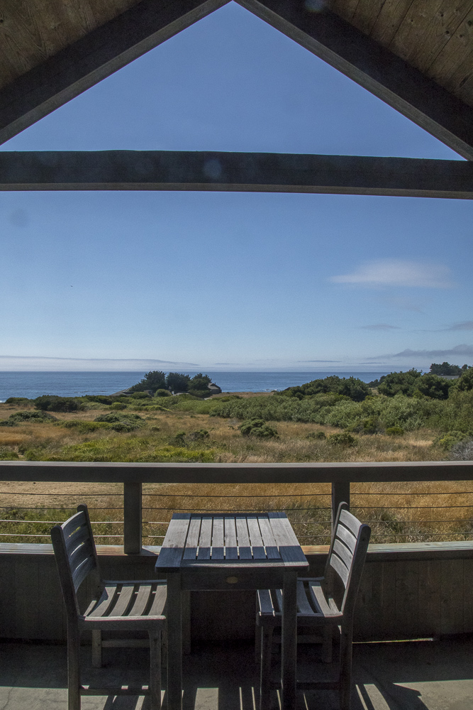 Deck with table, two chairs and view across meadow to ocean.