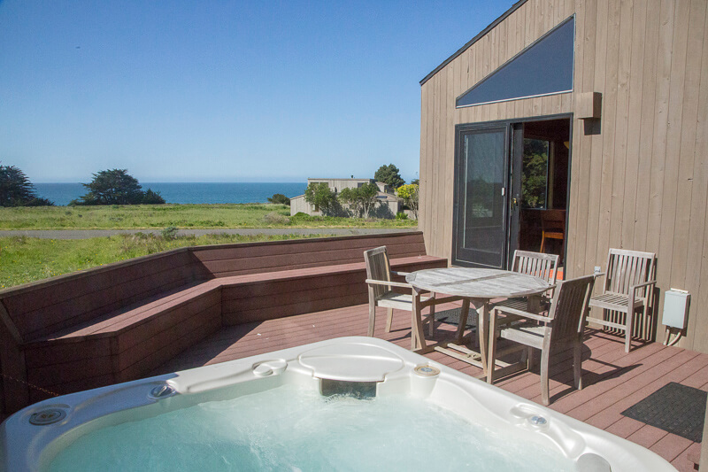Deck with table, three chairs and hot tub with a view across the meadow to the ocean beyond.
