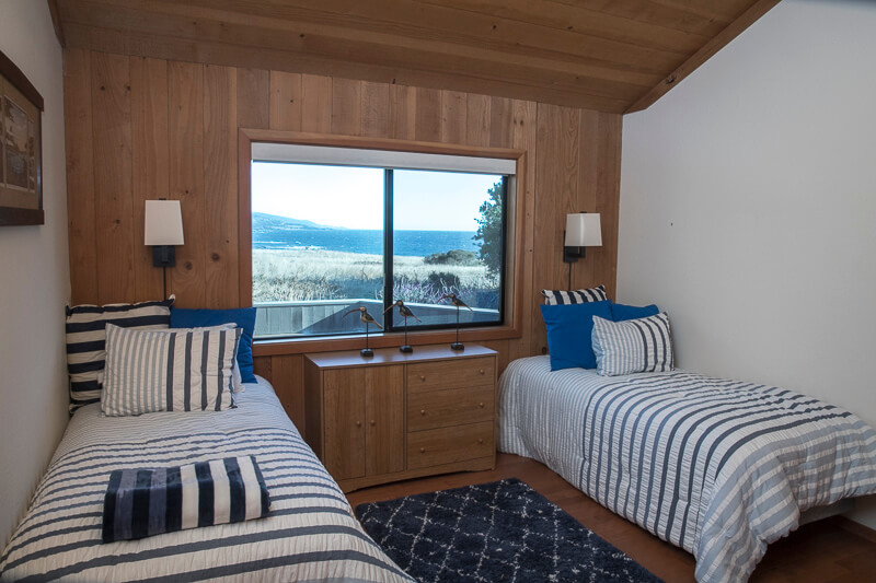 Bedroom with twin beds and view across meadow to ocean.