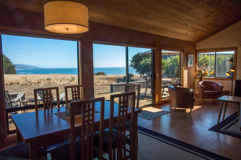 View of ocean across meadow from dining room - dining room table with six chairs.