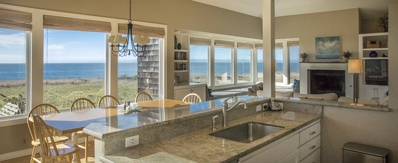 view from kitchen across dining room table to ocean