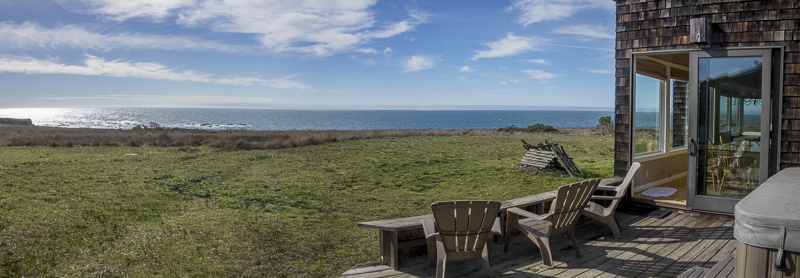 view of ocean across meadows from back deck