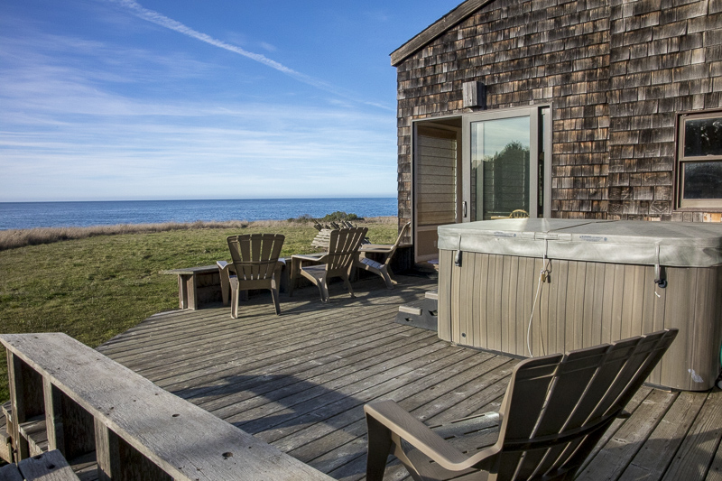 back deck with hot tub and view of ocean