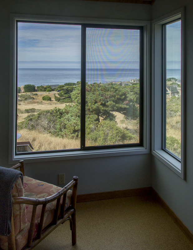 Chair and window with view across the meadow to the ocean.