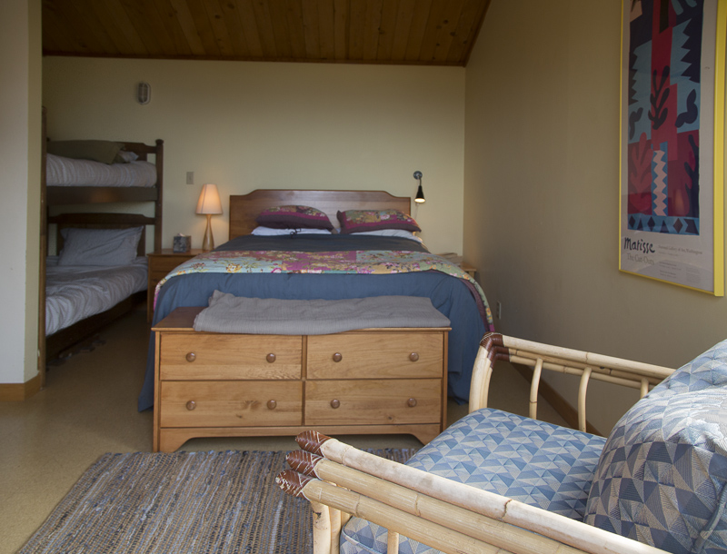 Bedroom with double bed, bunk beds, side table, lamp and a chair.