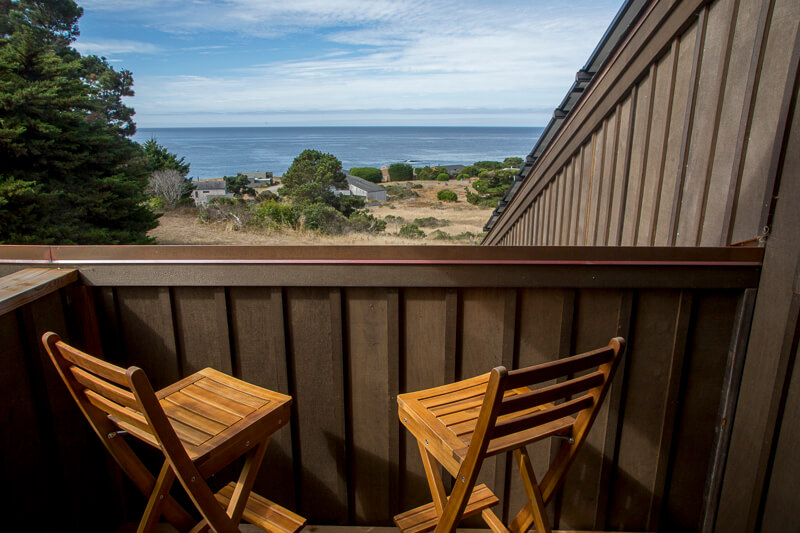 Two folding chairs on a deck with an ocean view.
