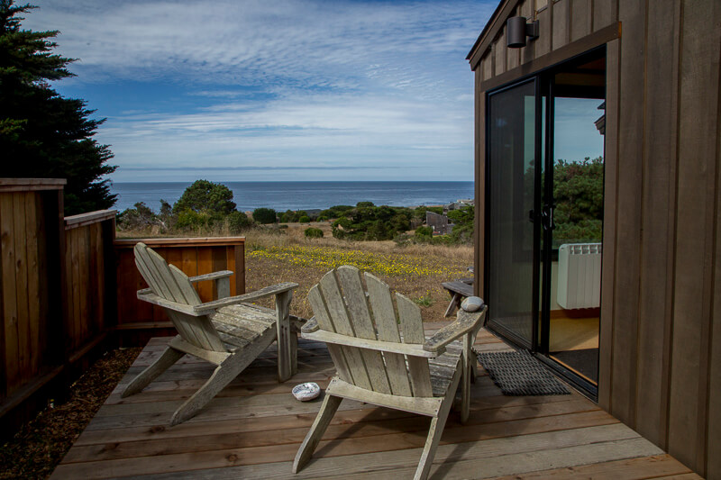 Deck, two chairs and view across meadow to ocean.