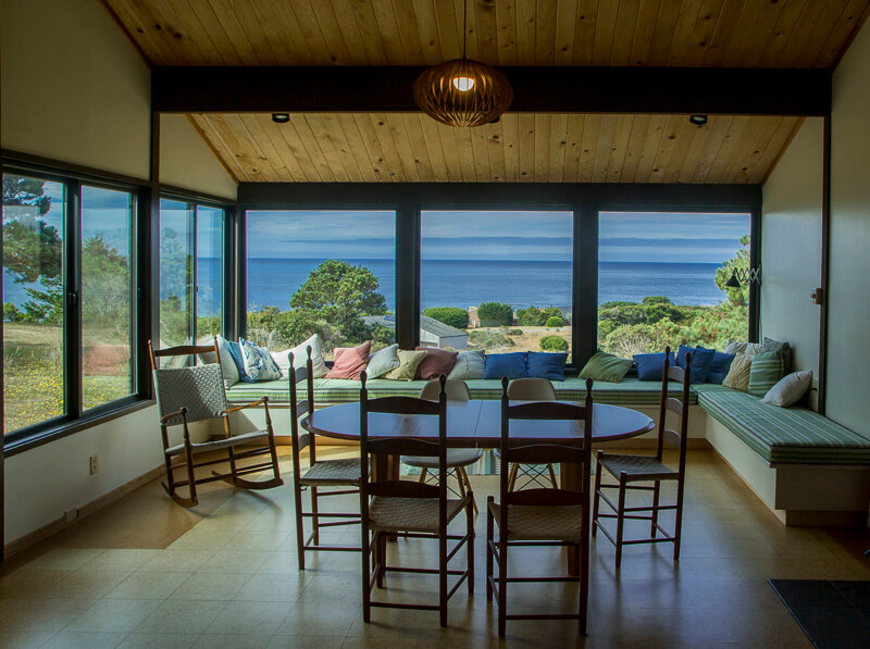 Dining area with dining table, six chairs, a rocker and a long window seat with a view of the ocean.