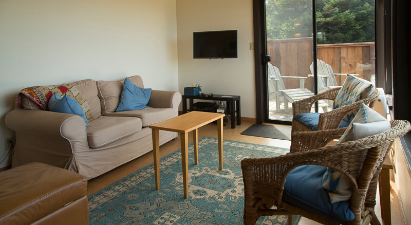 Sitting area with soca, coffee table, two chairs an ottoman and a wall mounted television screen.