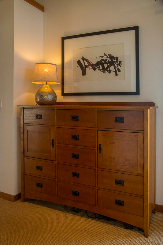 chest of drawers, painting and lamp in bedroom