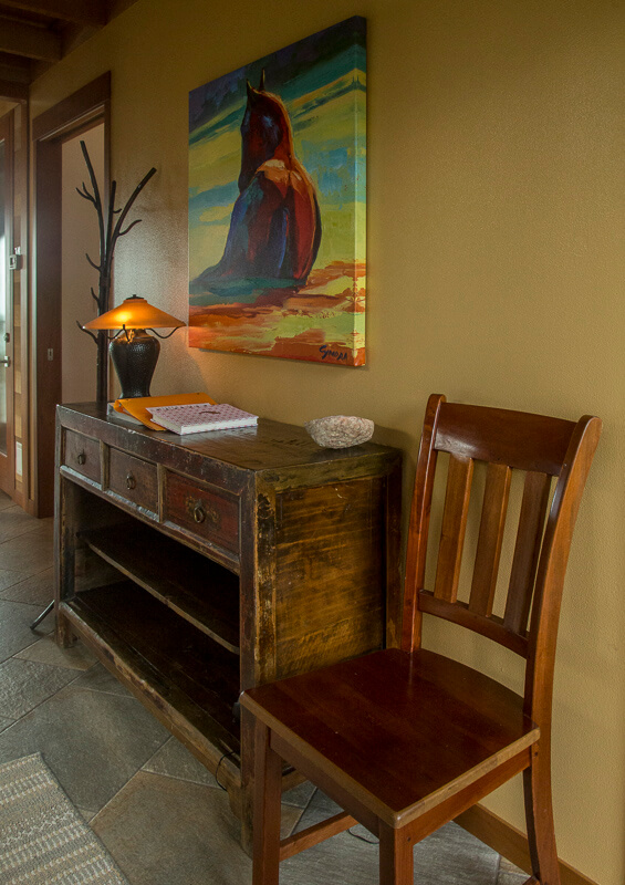 entry with painting, chair and cabinet