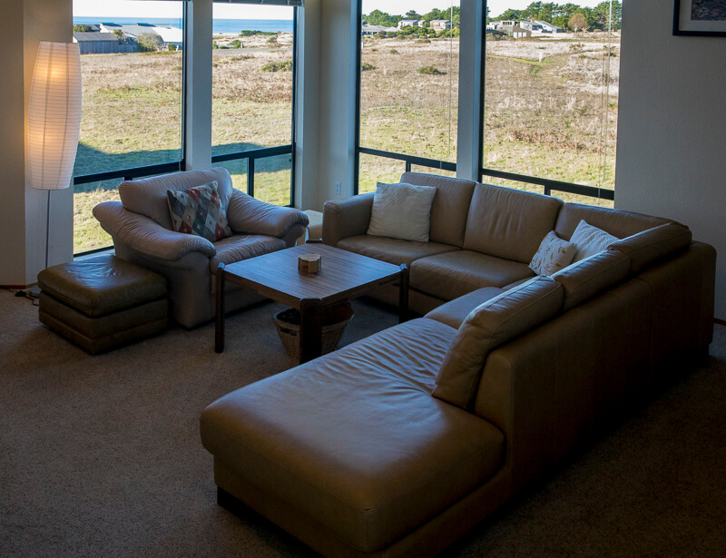 Living room with sofa, chair, ottoman, coffee table and view across meadow to the ocean.