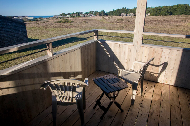 Deck, two chairs, small table and view of meadow to ocean beyond.