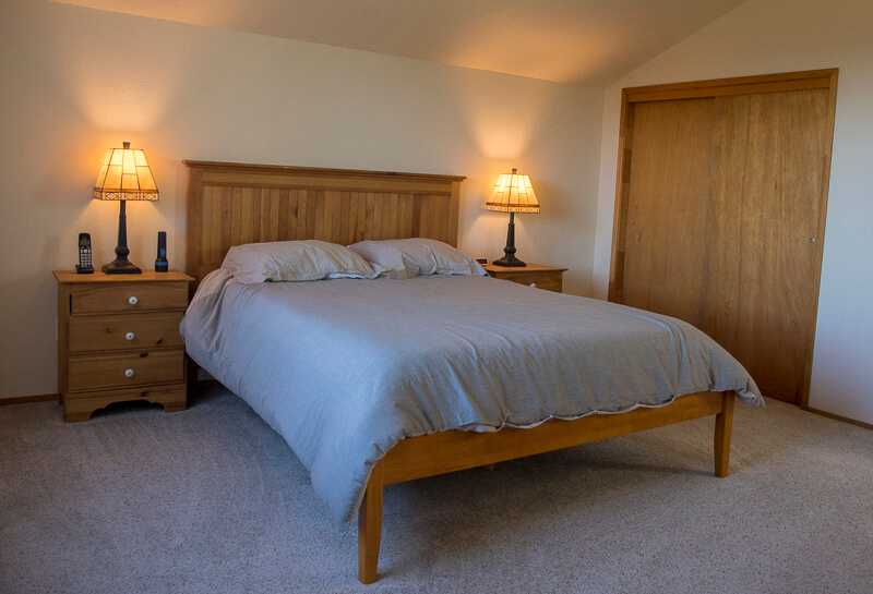 Bedroom with bed, two side tables and two lamps.