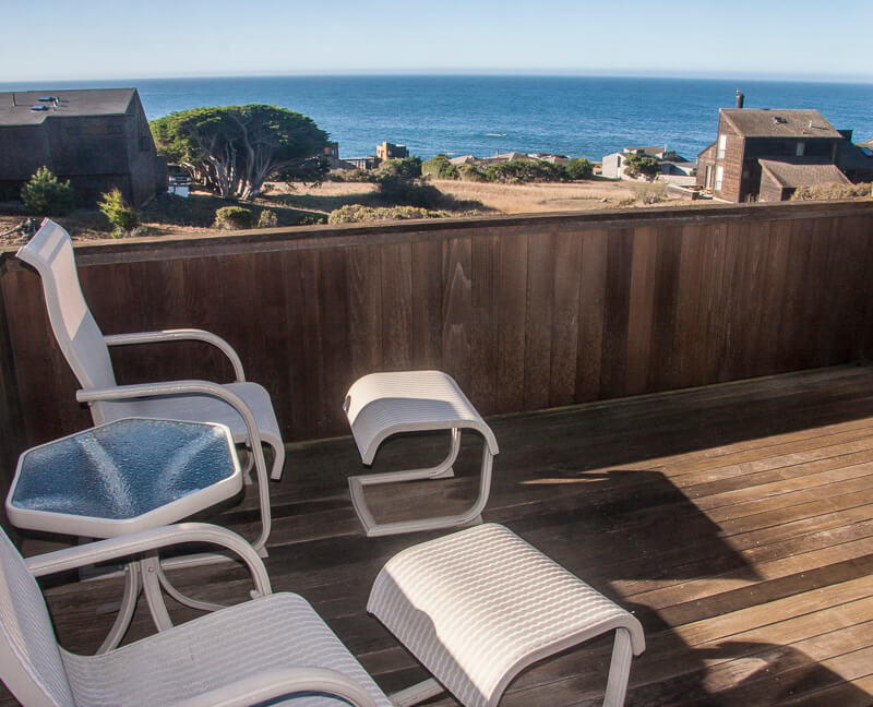 Deck with two chairs, two ottoman and view of ocean.