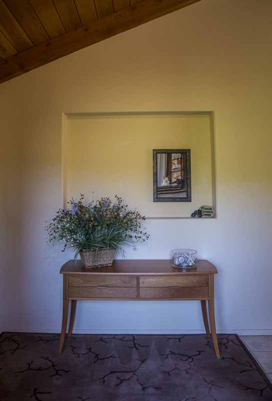 Entry vestibule showing table with flower arrangement..
