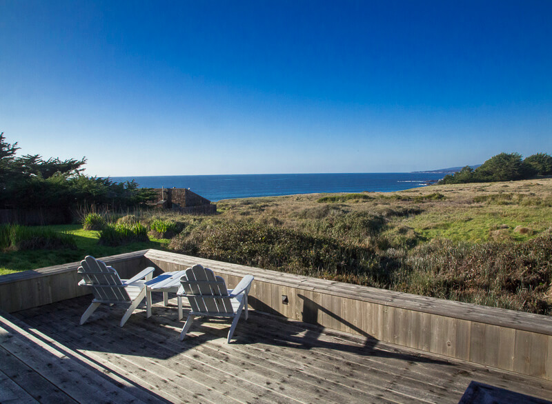Deck, two chairs, small table and view across meadow to the ocean.