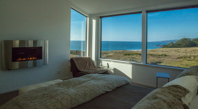 Bedroom with bed, chair, table, gas fireplace and views across meadow to the ocean.