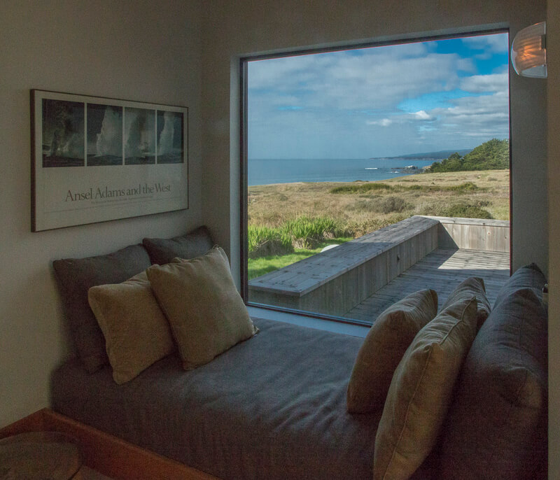 Window seat with view across meadow to ocean.
