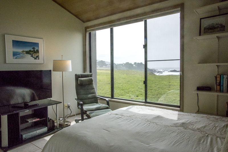 bedroom with view of meadow and ocean