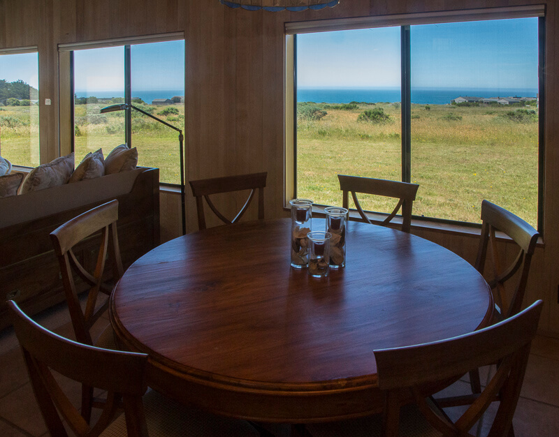 A round dining table with six chairs and a view across the meadow to the ocean.
