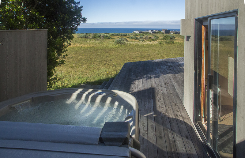 A deck with hot tub and view across the meadow to the ocean.