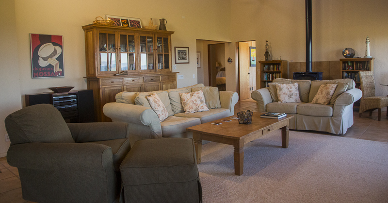 Living room with two sofas, a coffee table, chair with ottoman, a large cabinet and wood stove.