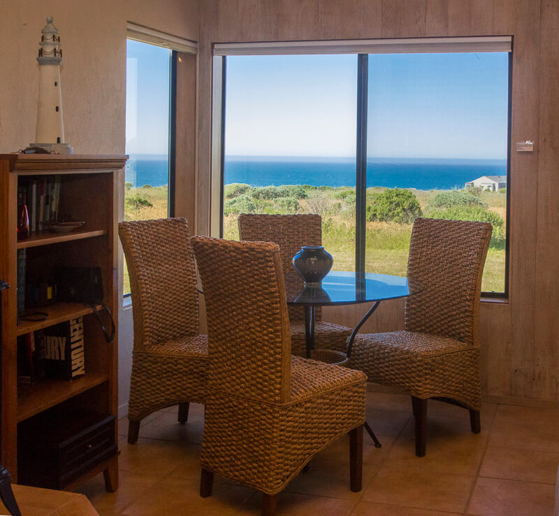 Glass table with four chairs, a bookcase and a view across the meadow to the ocean.