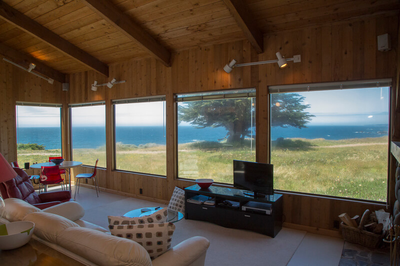 living room with view of meadow and ocean beyond