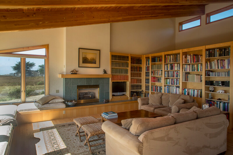 Living room showing book shelves and fireplace with a view of the meadow.
