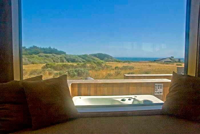 View across back deck with hot tub, across meadow to ocean from living room