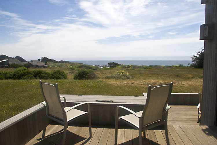 Deck with two chairs and a view across the meadow to the ocean.