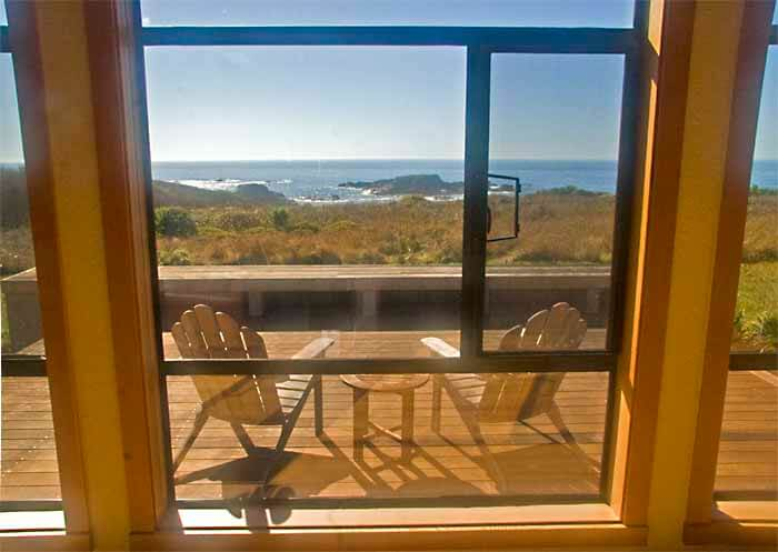 View from living room with back deck and chairs