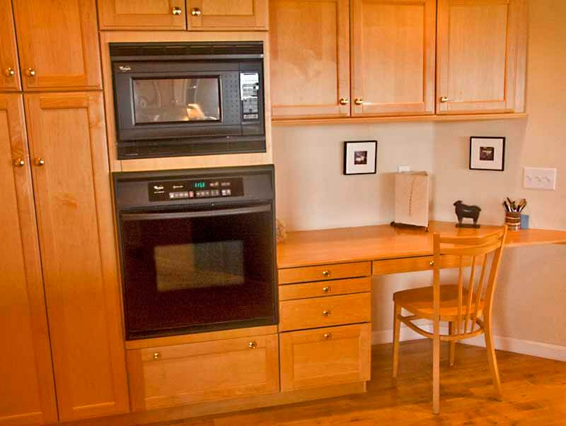 Kitchen showing wall oven and desk with chair.