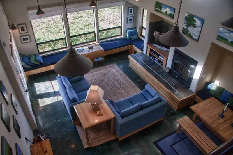 Living room seen from above with two sofas, corner table, window seat, fireplace, table, bench