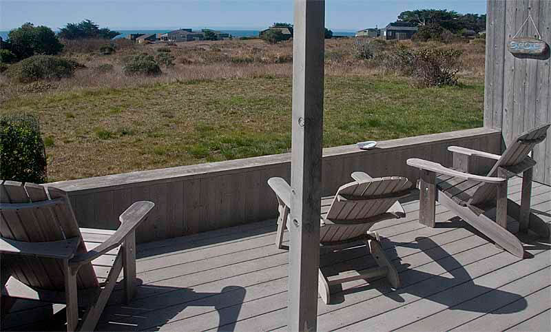 Deck with three chairs and view across meadow to ocean.