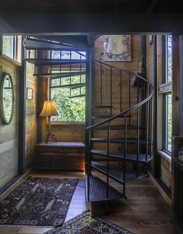 Spiral metal staircase, small chest with lamp.