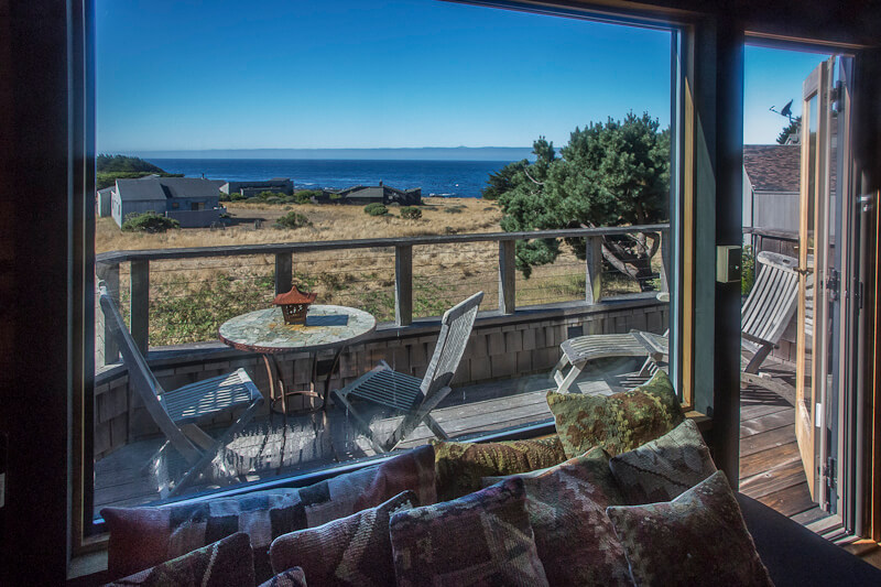 Living room looking out onto deck with small table three chairs, one ottoman and a view to the ocean.