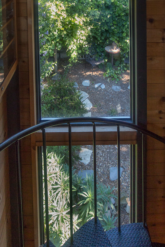 Window looking out onto garden from metal spiral staircase.