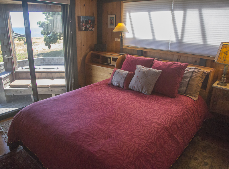 Bedroom with headboard cabinet and two lamps.  Deck outside window.